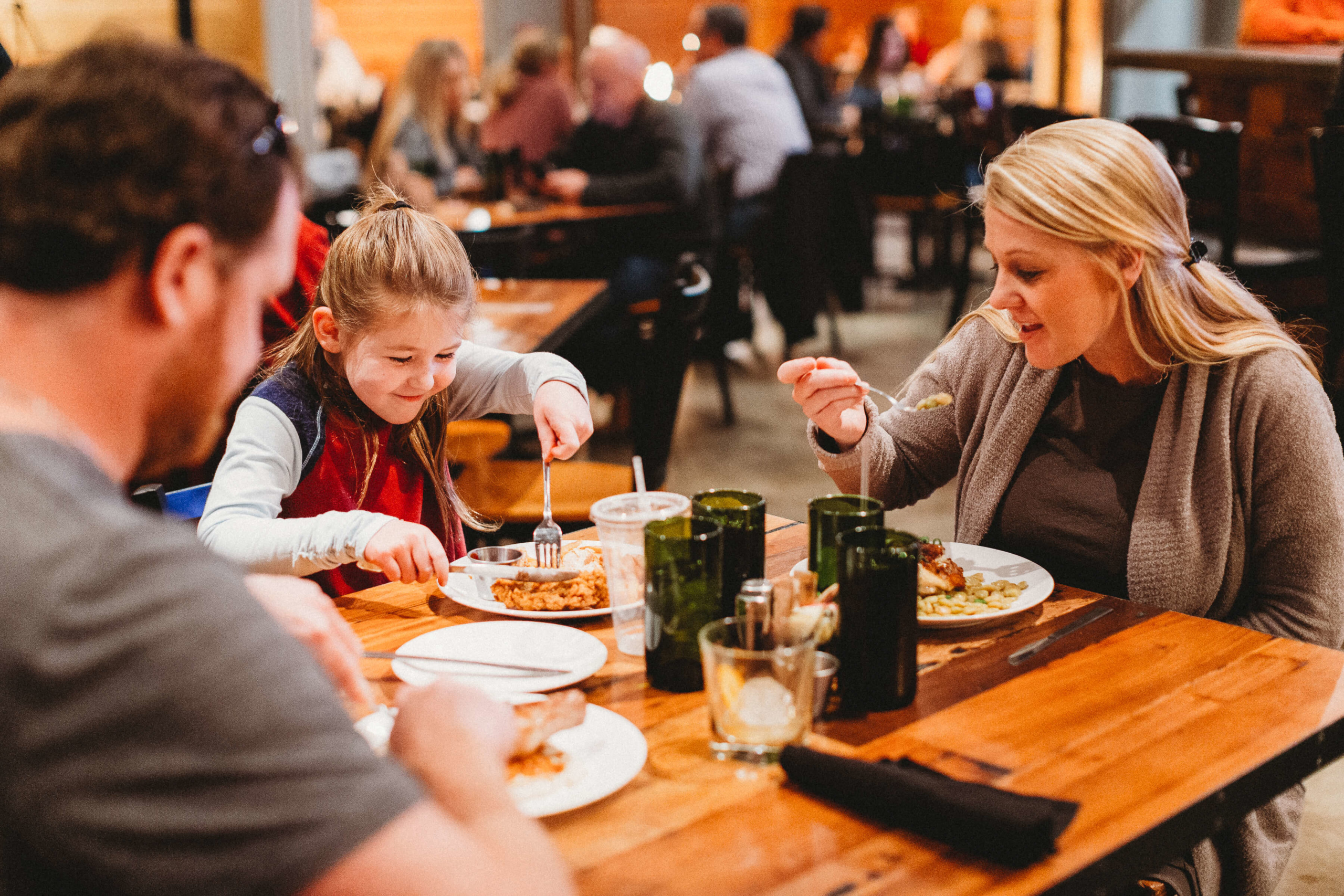 Little girl eating a beautiful dish while surrounded by her smiling parents, also enjoying their meals