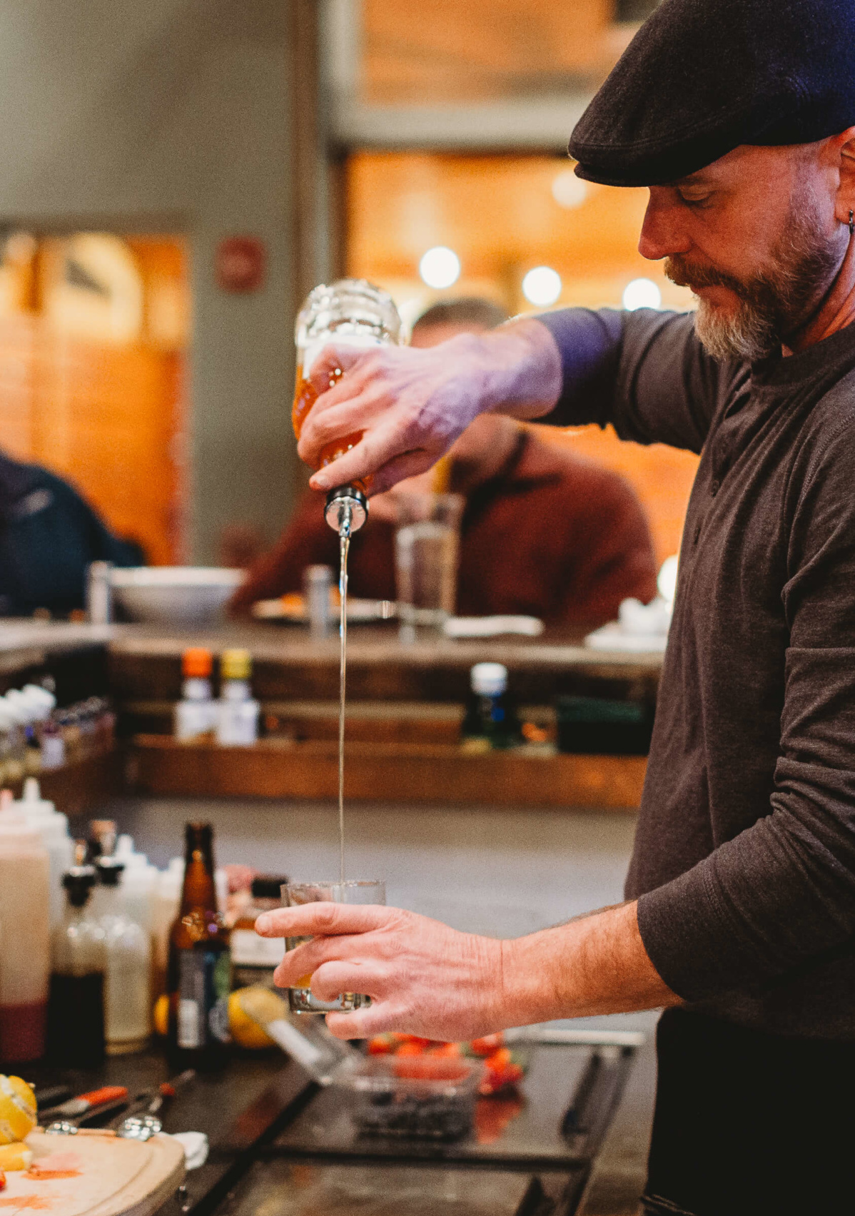 Male bartender pouring a cocktail behind a modern stylish bar